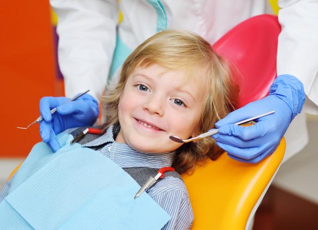 Menino sentado numa cadeira de dentista sorrindo e sendo examinado