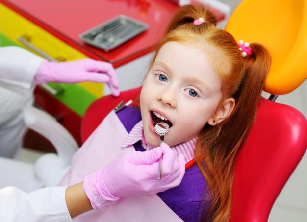 Menina sentada numa cadeira de dentista sendo examinada e com a boca aberta