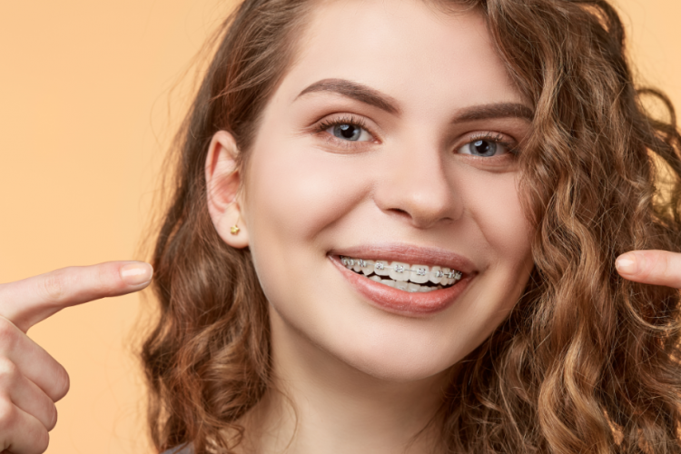 Adolescente sorrindo com aparelho fixo apontando para a boca com as mãos