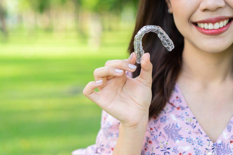Mulher segurando aparelho transparente e sorrindo - Orthoclin