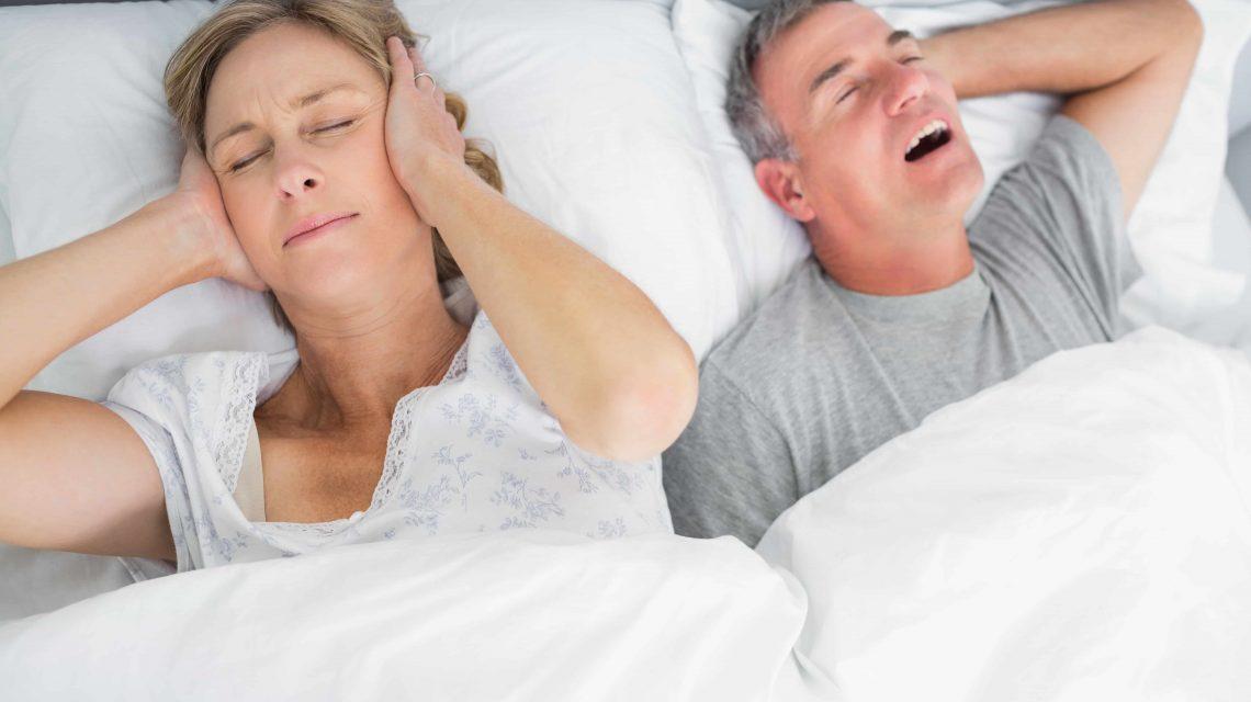 Mulher tampando os ouvidos enquanto o marido ronca na cama