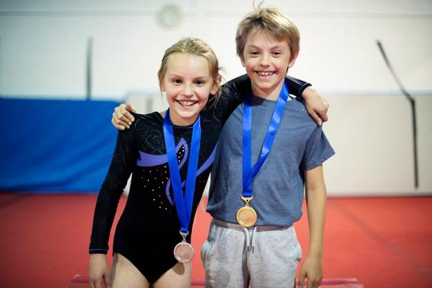 Menino e menina sorrindo em cima de um pódio com medalhas no pescoço - Orthoclin