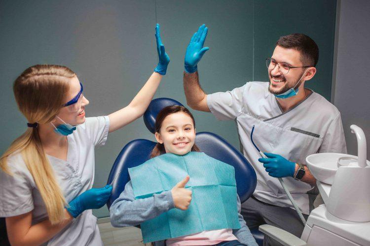 Dentistas sorrindo e se cumprimentando enquanto menina com mordida cruzada sorri na cadeira