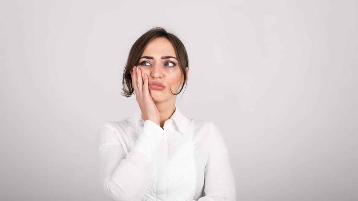 Mulher com a mão na mandíbula sentindo dor - Artigo Orthoclin