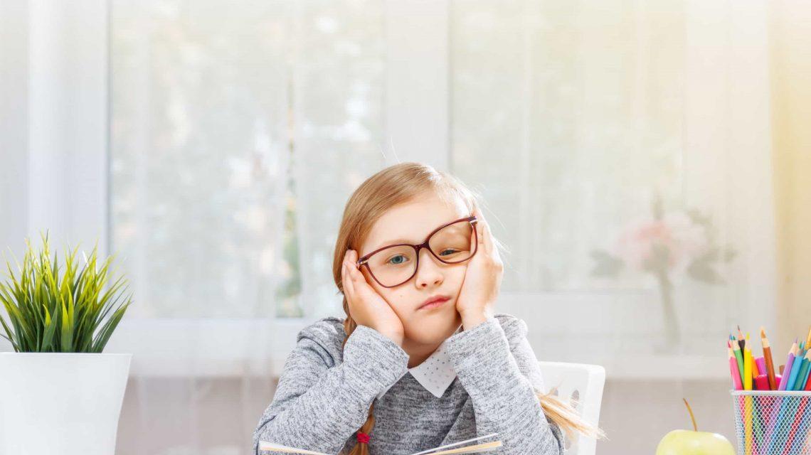 Uma estudante cansada está sentado em uma mesa com uma pilha de livros - Artigo Orthoclin