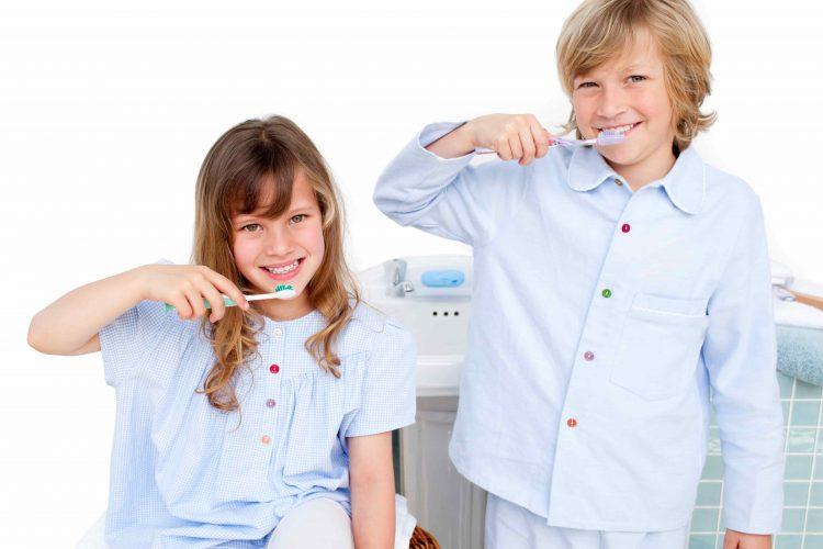Crianças sorrindo enquanto escovam os dentes - Orthoclin