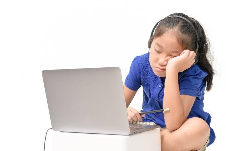 Criança na frente de um laptop com sono