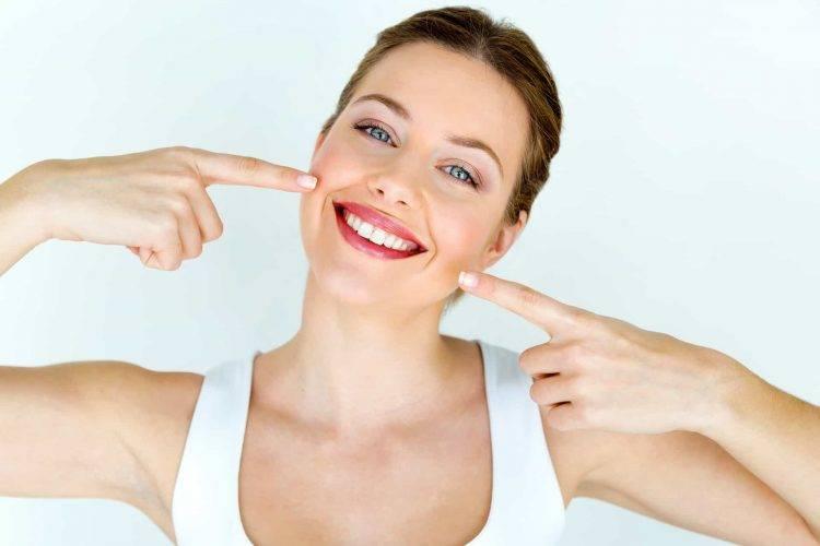 Mulher sorrindo e apontando os seus indicadores para o seu sorriso