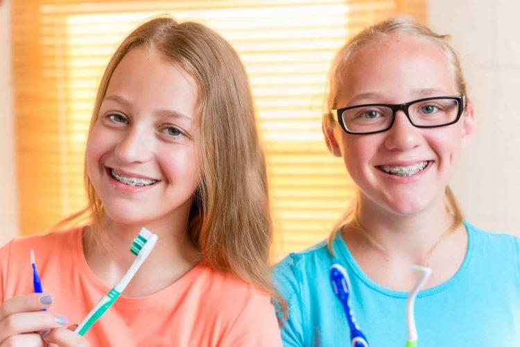 2 meninas sorrindo segurando escovas de dentes